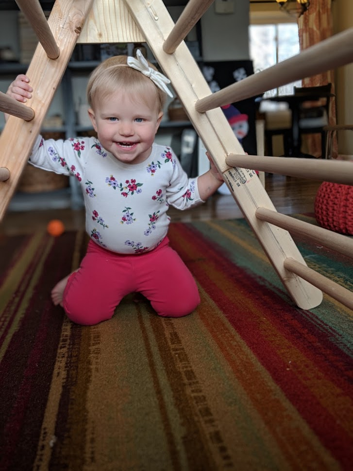 a girl toddler smiling under a DIY climbing structure in a living room