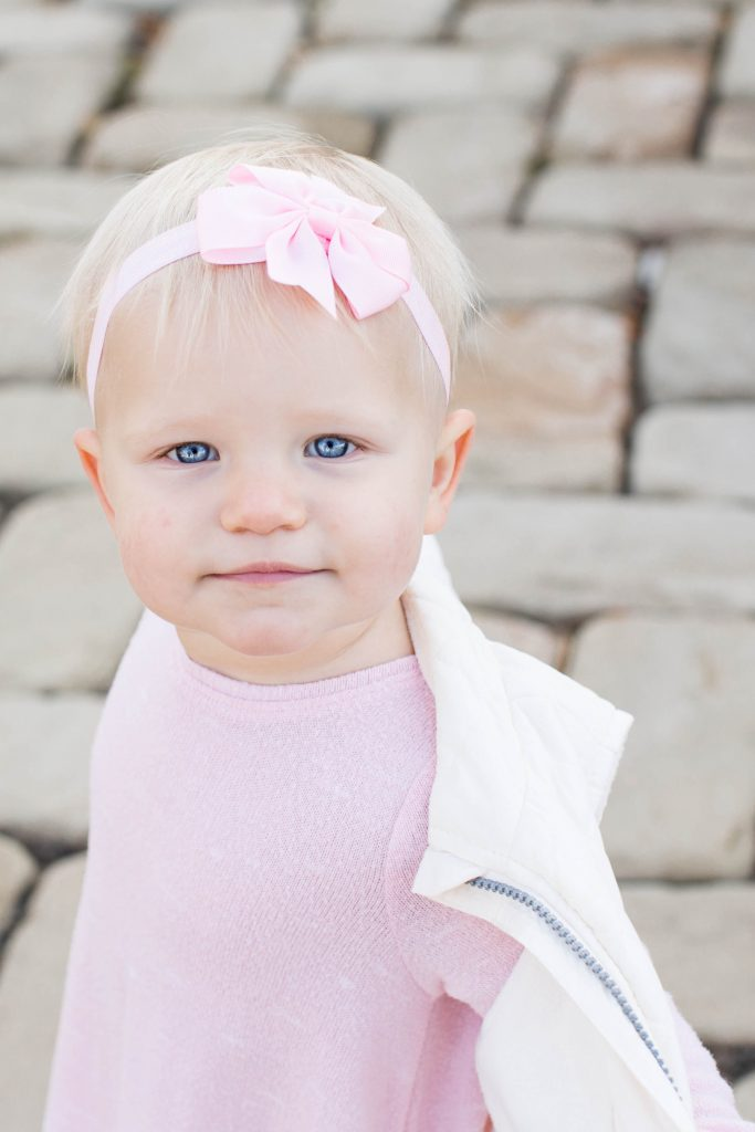 a toddler with white blonde hair and vivid blue eyes dressed in a pink sweater