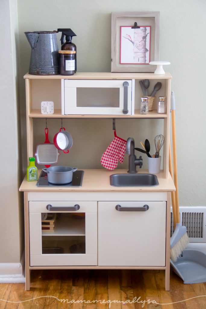 the IKEA play kitchen set up as a toddler play space in the dining room