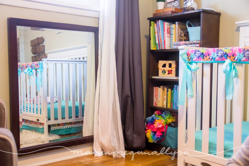 A low mirror and a bookshelf with some toys and dress up clothes for a toddler play space in a bedroom