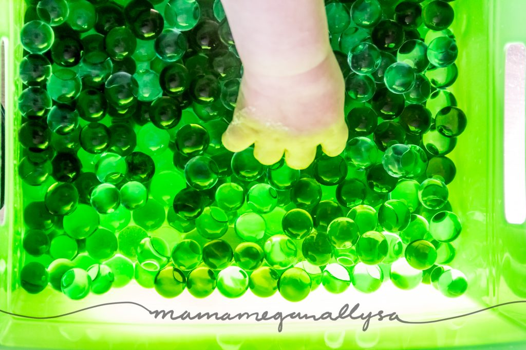 a toddler hand reaching into the green waterbeads