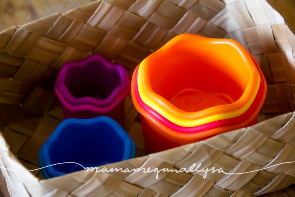 Brightly colored stacking cups nested in a basket