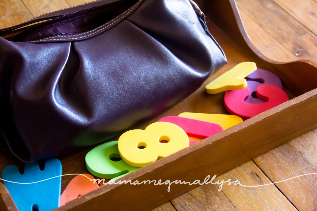 her purple purse and foam letters in a wooden tray
