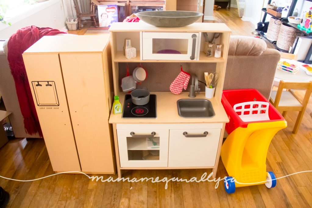 a toddler shopping cart and ikea play kitchen with thrifted play fridge