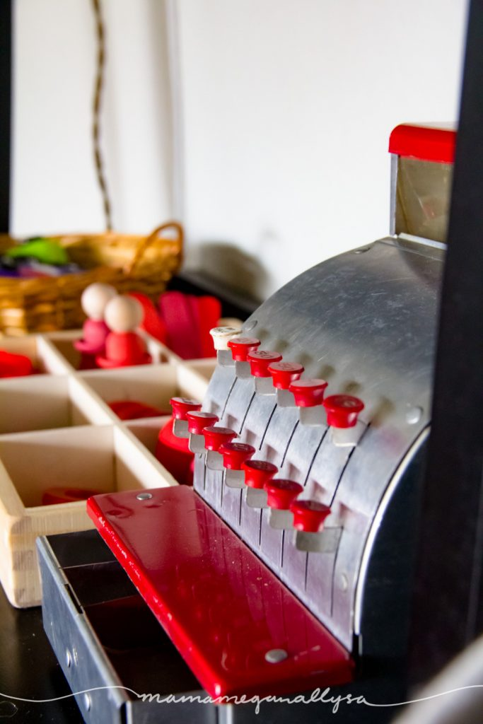 a close up of a vintage metal cash register on a toy shelf