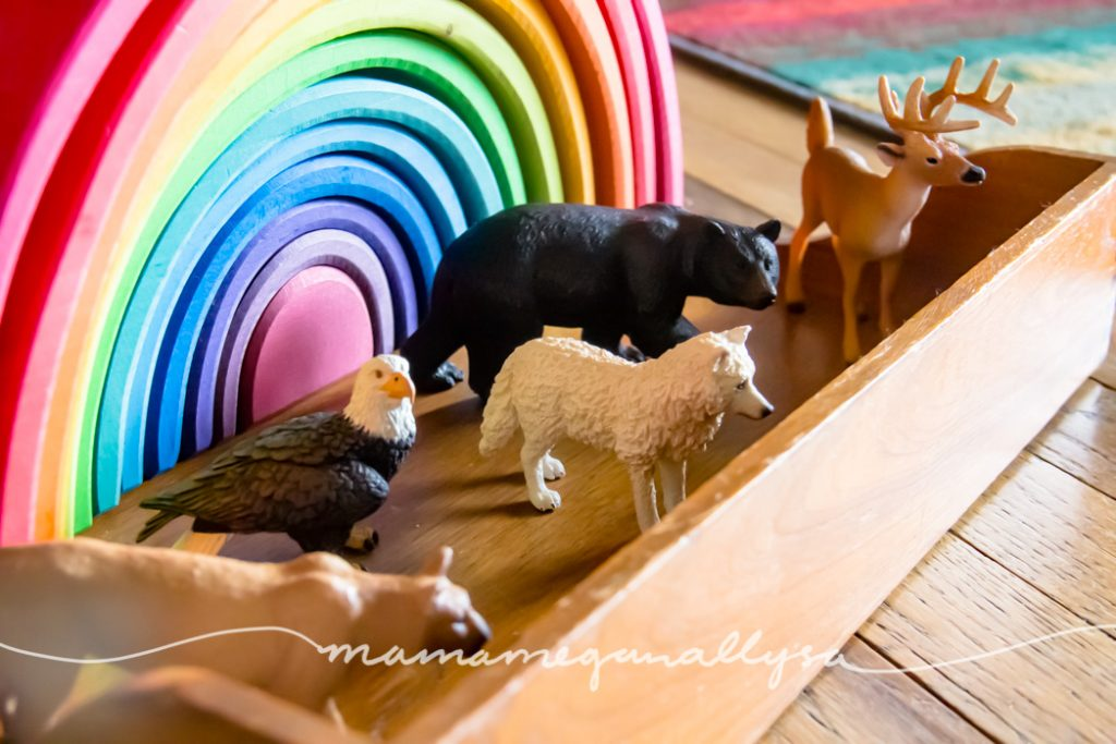 a Grimms rainbow stacker toy with forest animal figures in front of it