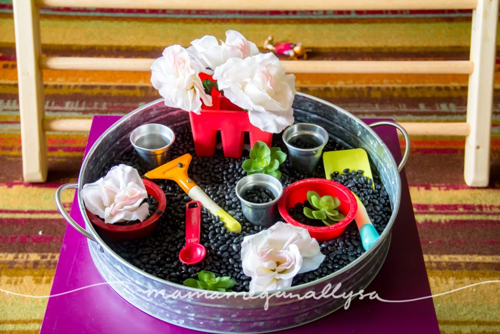 a black bean garden sensory bin containing red bowls, silver pots, fake flowers, and gardening tools