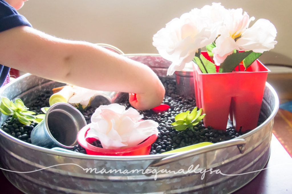 a toddler scooping beans with red measuring spoon in a garden sensory bin