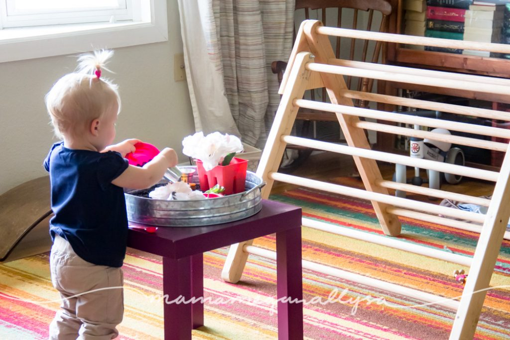 a toddler playing at a play table with a sensory bin in a living room