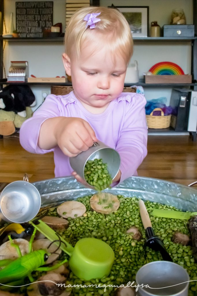 a toddler pouring split peas out of a little metal pot into a forest themed sensory bin