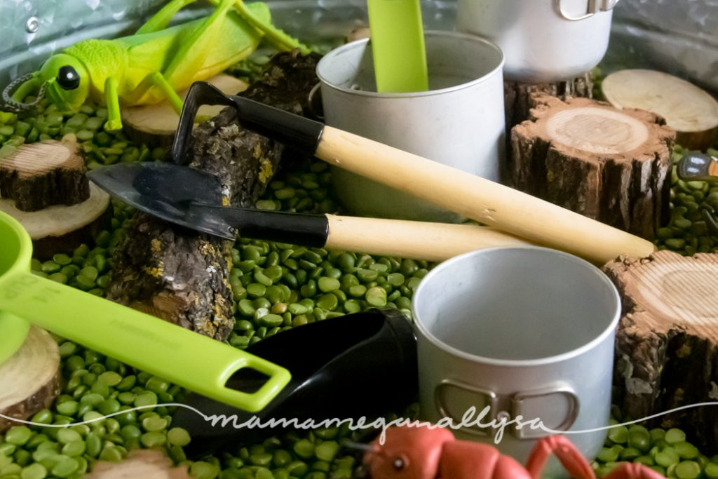 A close up of the mini garden tools, wood slices and mini metal pots