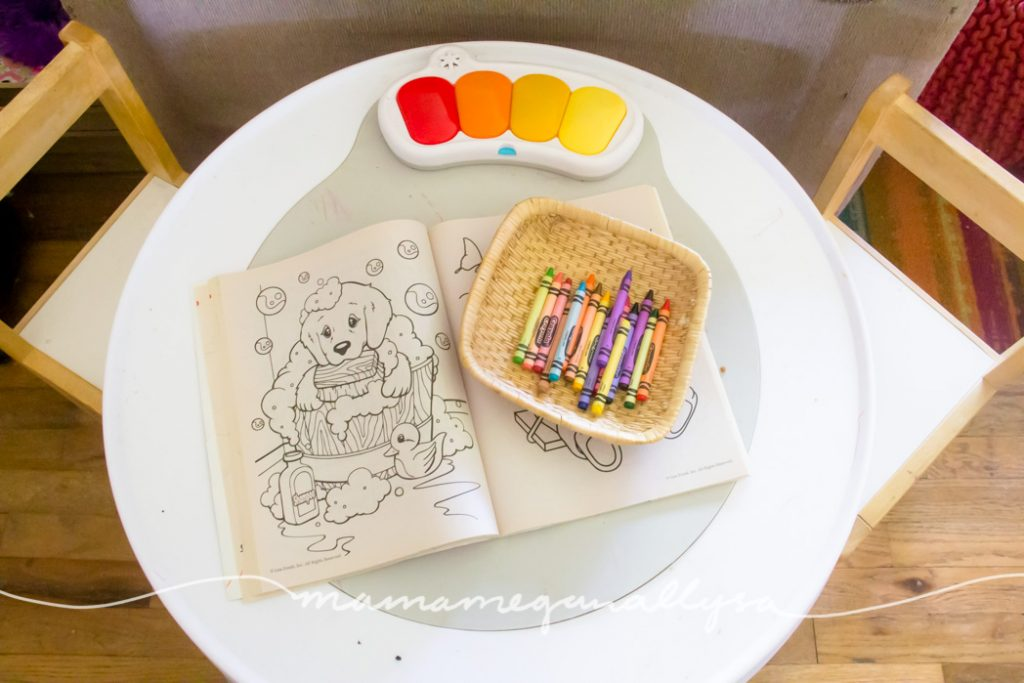 a lisa frank coloring book on an activity table with a small tray of crayons