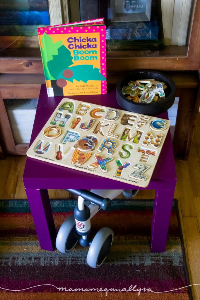 a small table with an ABC puzzle and small tray full of pieces with a baby bike tucked under it