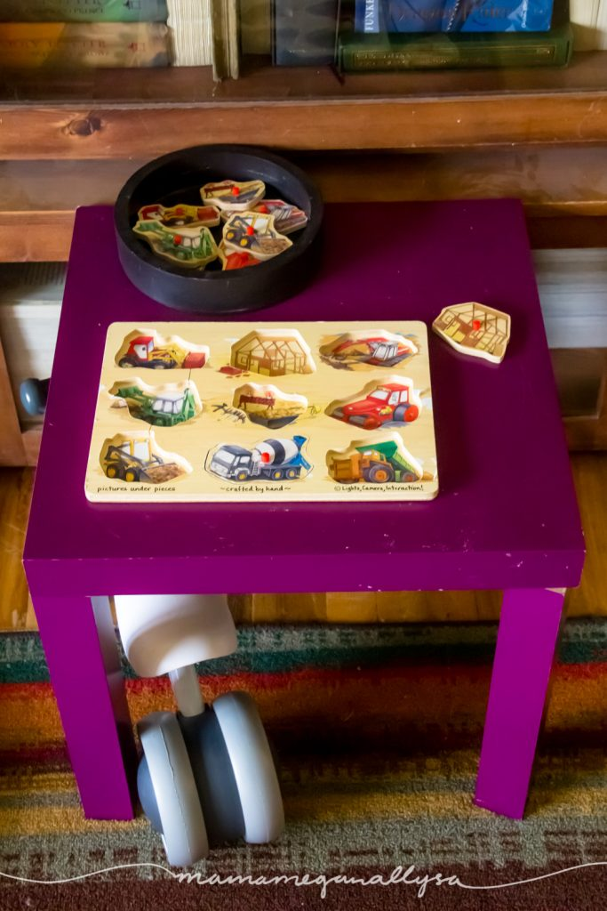 a wooden construction themed peg puzzle on a small table with a baby balance bike under it