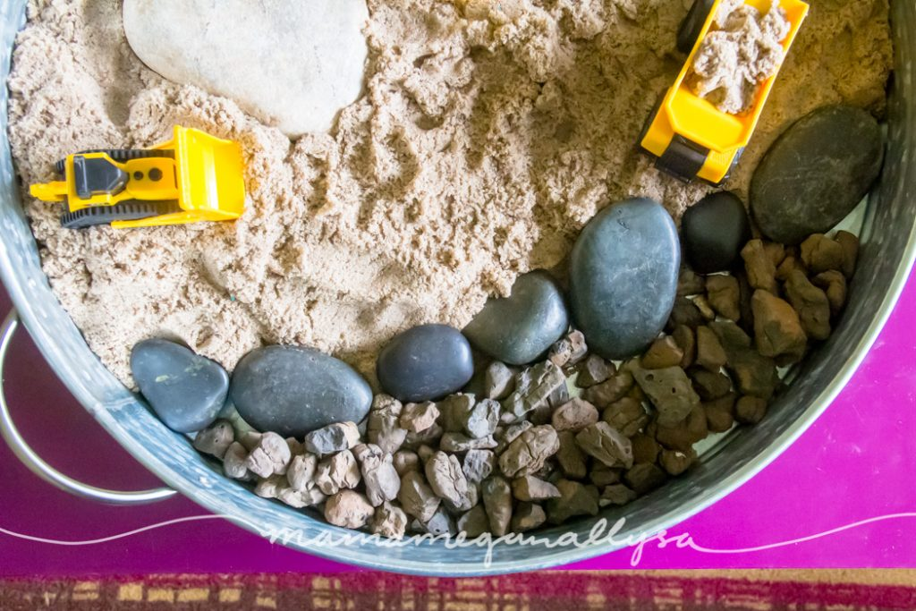 a close up of the large smooth black rocks and the smaller rought lava rocks as well as the kinetic sand