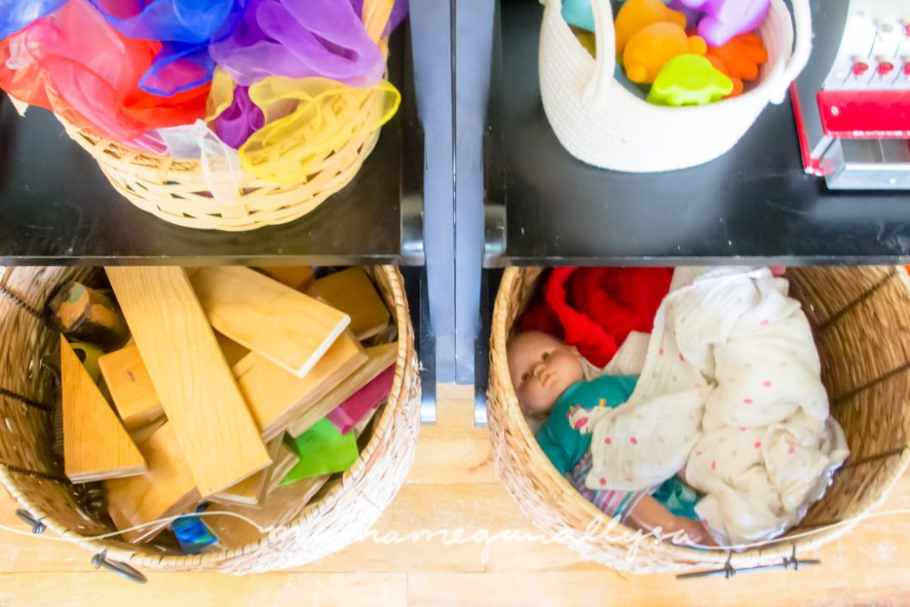 a top down view of her large baskets that hold her blocks and her babydolls on her toddler toy shelf