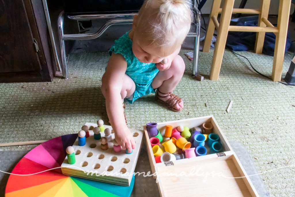 a toddler squatting down on the shop floor to play with the peg person board loose parts tool
