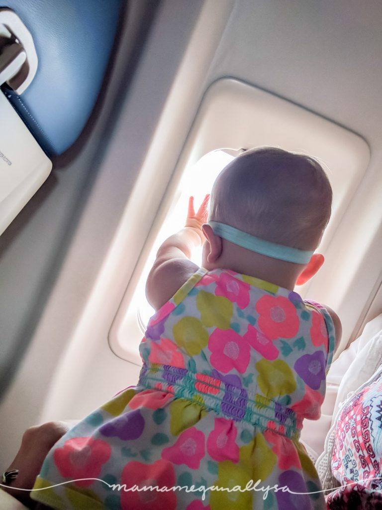 a toddler looking out the window of an airplane