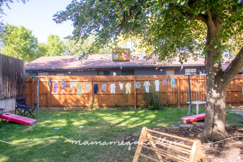 a overview of our backyard showing the clothesline with baby clothes, cornhole, pikler tirangle and the gender reveal box hanging in our tree
