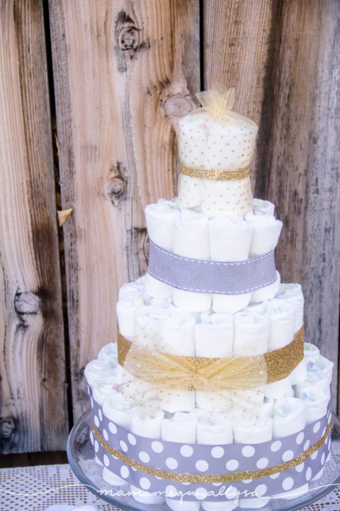 a diaper cake with grey and gold ribbons decorating it