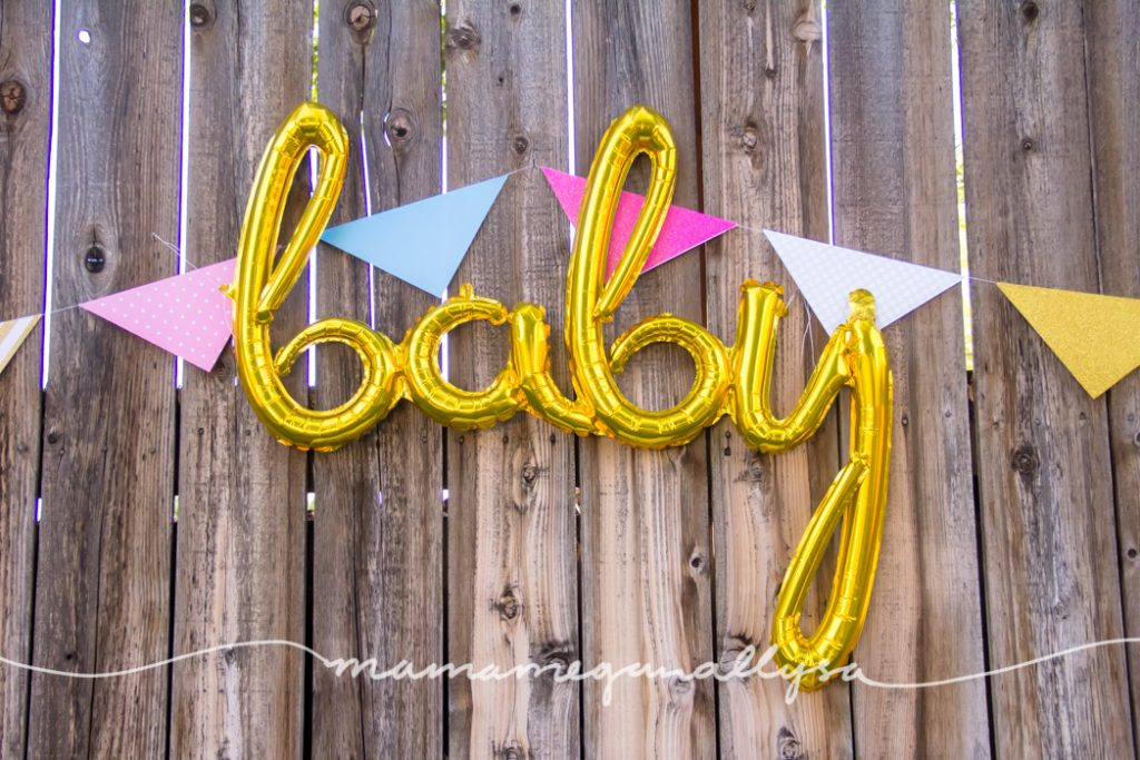 a gold cursive mylar balloon hung along with a pink and blue paper banner on our back fence