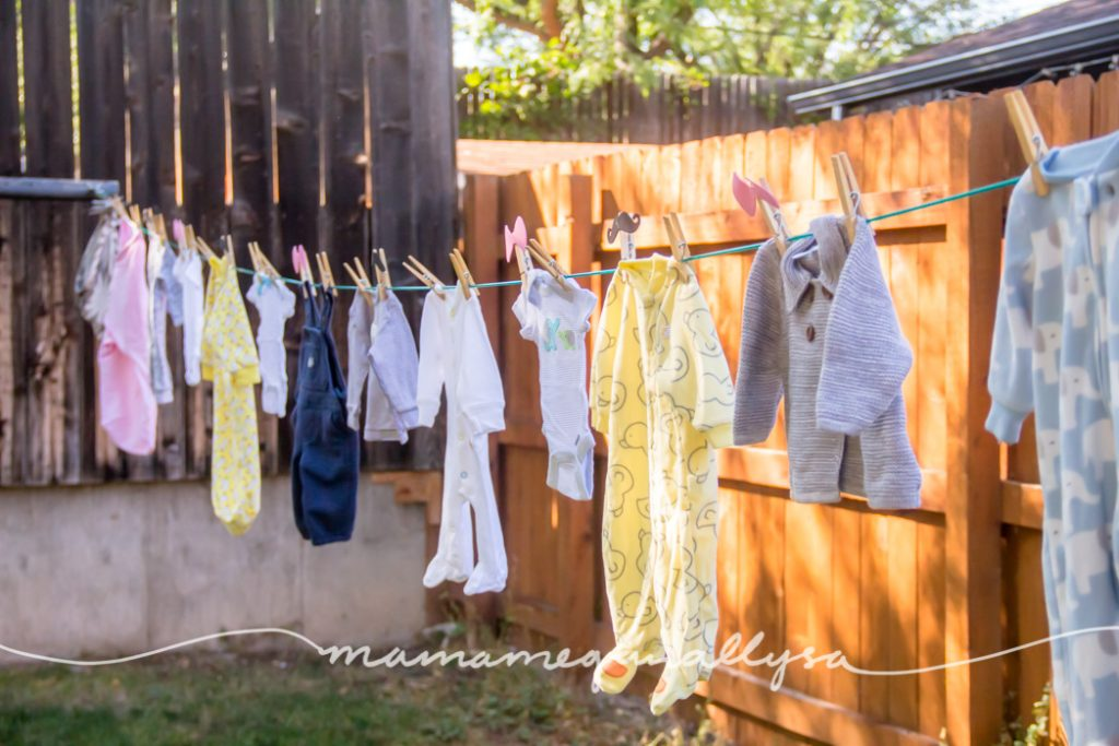 a line of baby clothes hung up for decor as well as my gender reveal themed clothes pins. Bows for girls and mustaches for boys