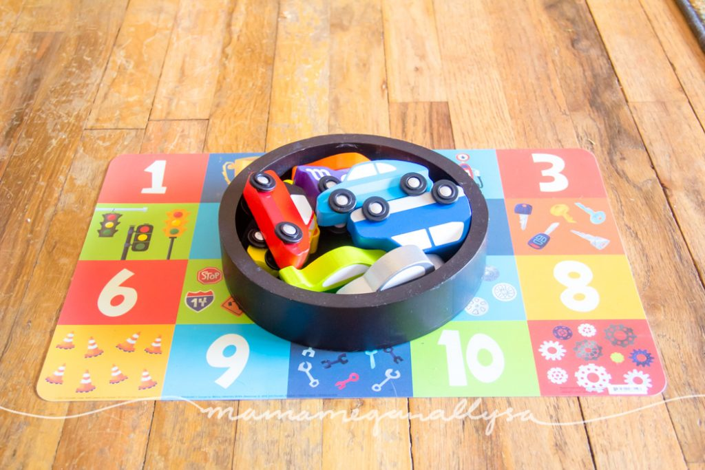 cars presented in a small basket with a placemat stored under as an invitation to play