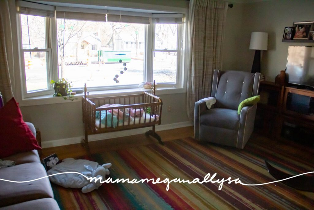 The baby side of the living room with the rocking chair and play mat for tummy time as well as the cradle and mobile set up in front of the window