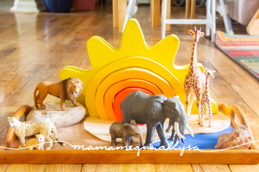 I pulled together a simple safari small world for our springtime toy rotation. It included our bright yellow sun stacker and some moms and baby family units
