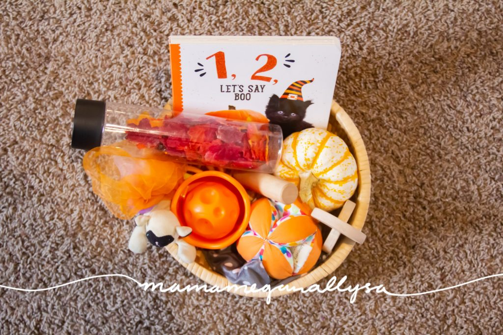 A discovery basket is a simple collection of items that are safe for the babe to explore and learn about at their leisure. I themed this basket loosely around Halloween with lots of orange and some pumpkins!