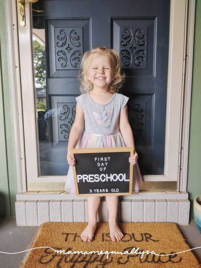 a picture of a 3 year old girl smiling big and holding a letterboard that says first day of preschool