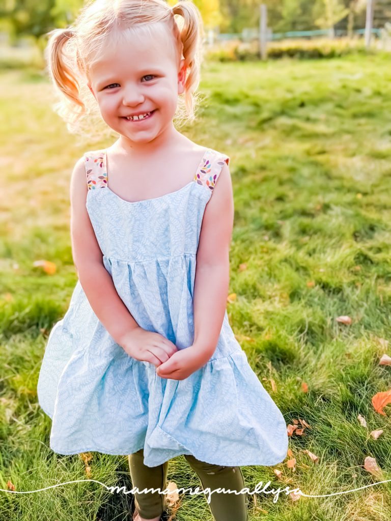a blonde three year old with pigtails wearing a dress smiling  at the camera