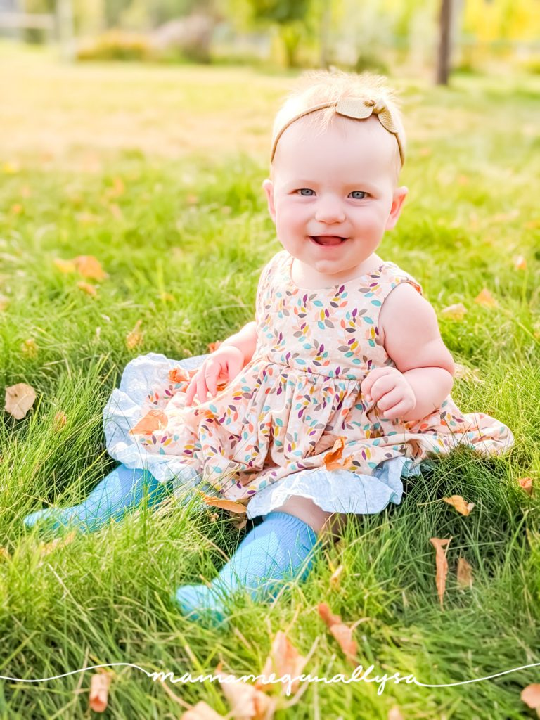 a baby sitting in the grass, wearing a dress and smiling at the camera