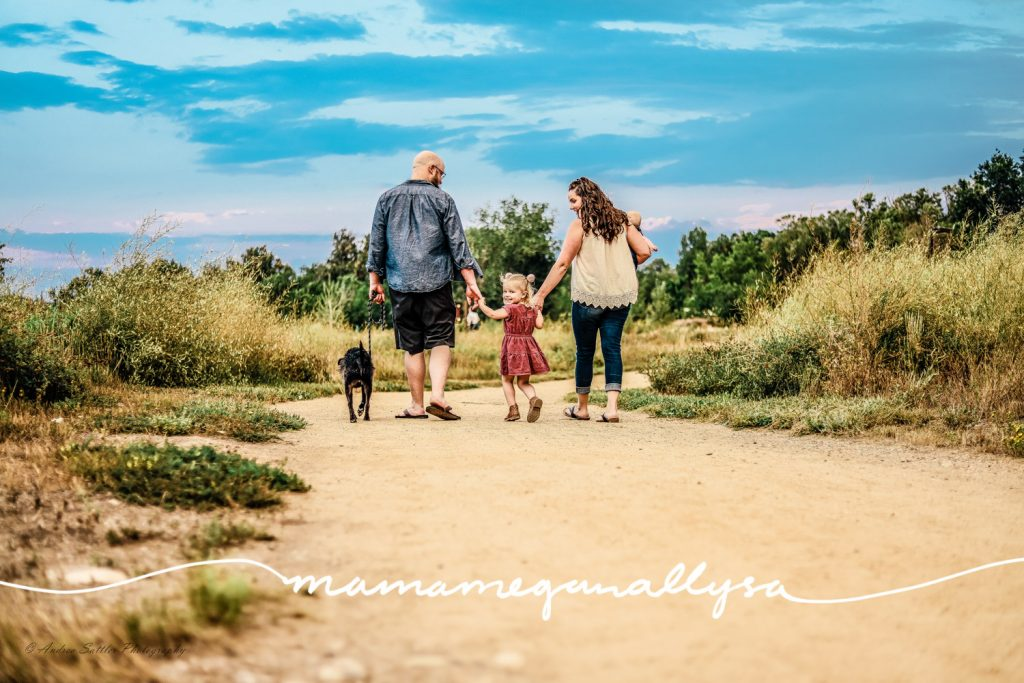 a family walking away from the camera and the 3 year old girl looks back over her shoulder at the camera