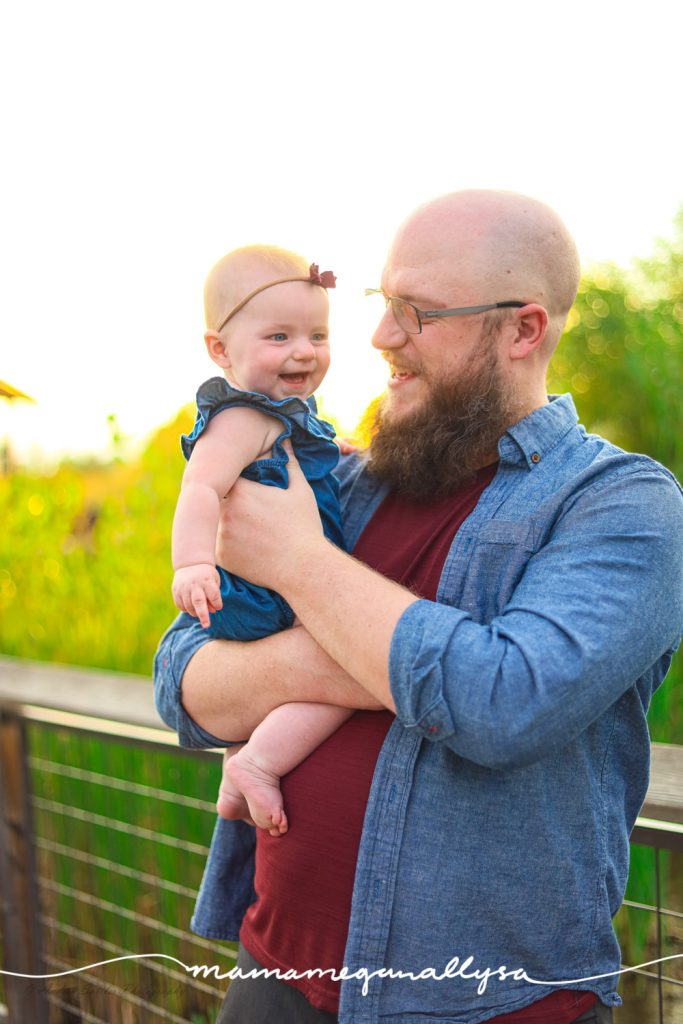 a dad holding and laughing with a baby  with the sunset behind them