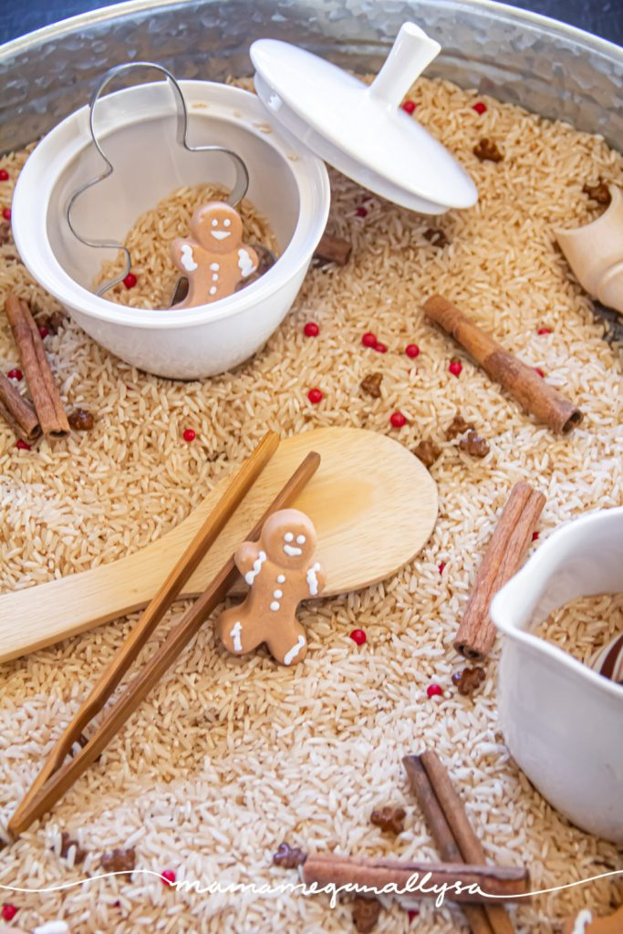 a detail shot of the set up in our gingerbread sensory bin. Using rice sented as gingerbread as the filler and sprinkles and cinnamon sticks mixed in. There are also gingerbread man candies scattered around as well as a gingerbread man cookie cutter and a couple other little tools and a creamer and sugar bowl for pouring