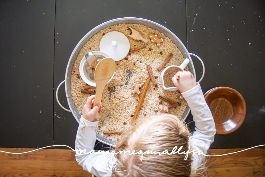 an overhead shot of a toddler playing in a gingerbread rice sensory bin