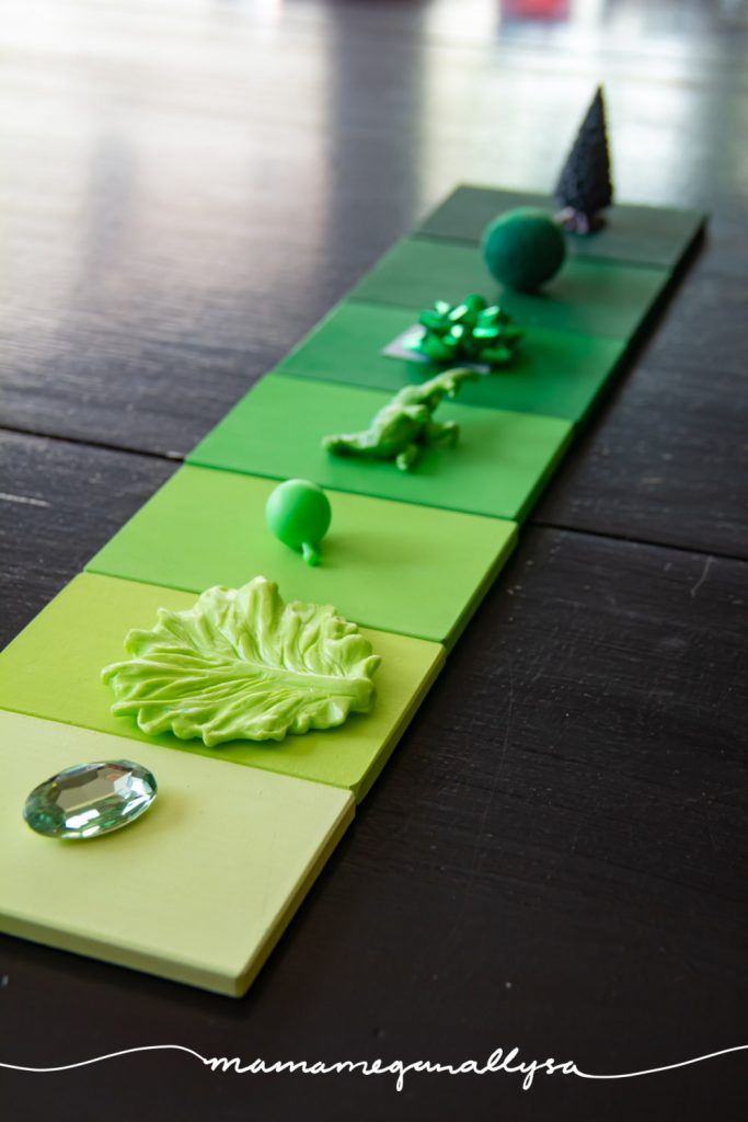 A line of green color tablets arranged in a gradient from light to dark with a small object that matches the color placed on top of each tile