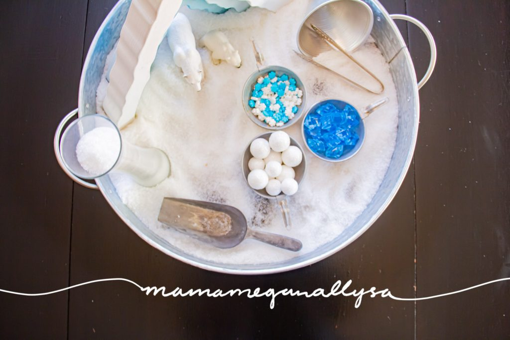 "an arctic small world sensory bin filled with Epsom salt, a wooden ice cave stacker standing in the back of the tray with a mama polar bear and per cub stand in the shelter. Some metal tools including a funnel, tongs and a candy jar scoop. Blue crystals, white ""snowballs"" and some snowflake sprinkles in little pans and a tall skinny glass vase filled with ""snow"""