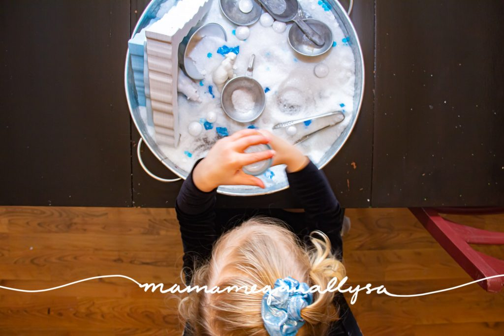 an overhead shot of a toddler having fun while she plays with an arctic small world sensory bin