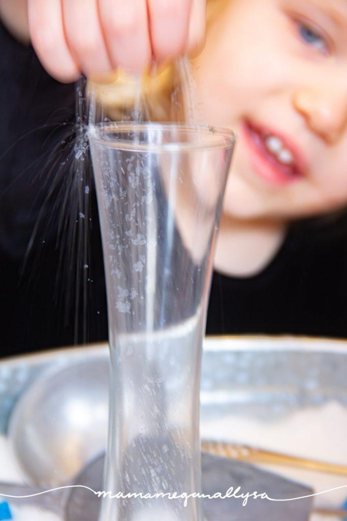 "a toddler sprinkling Epsom salt ""snow"" into a glass vase"