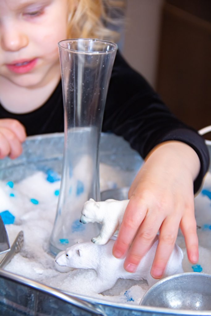 a toddler playing with a mama polar bear and her cub in an arctic small world sensory bin