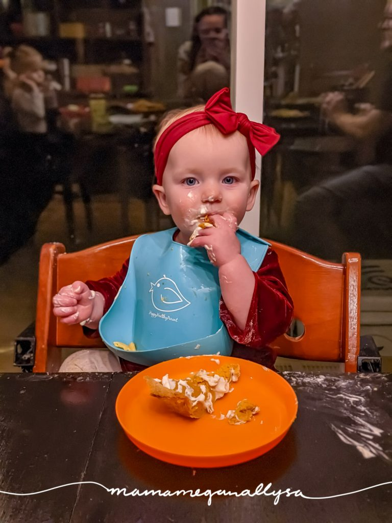 a baby eating her first slice of pumpkin pie
