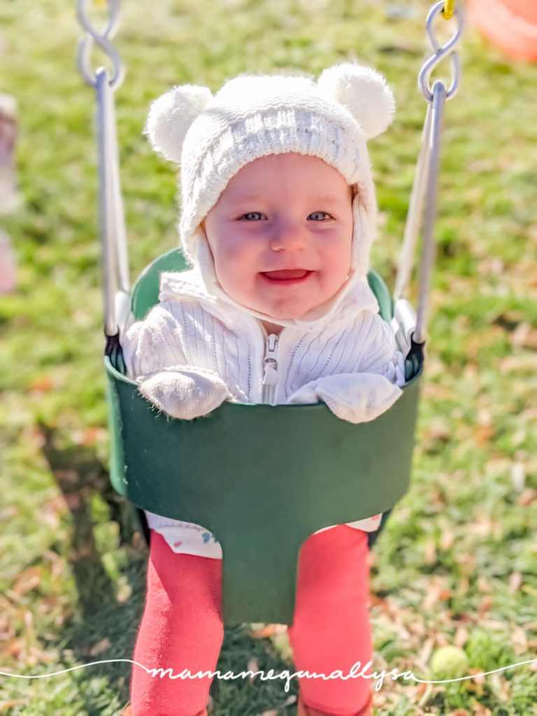 a baby smiling in a swing wearing a white pompom hat and white sweater