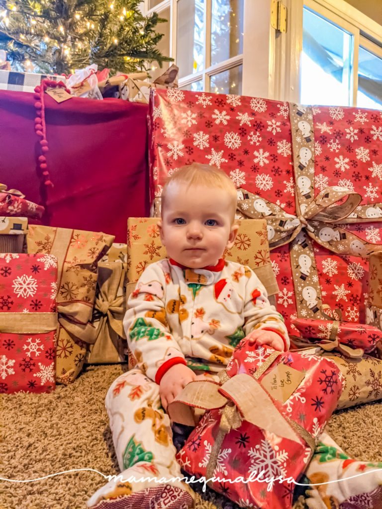 a baby wearing footed Christmas jammies and surrounded by Christmas presents