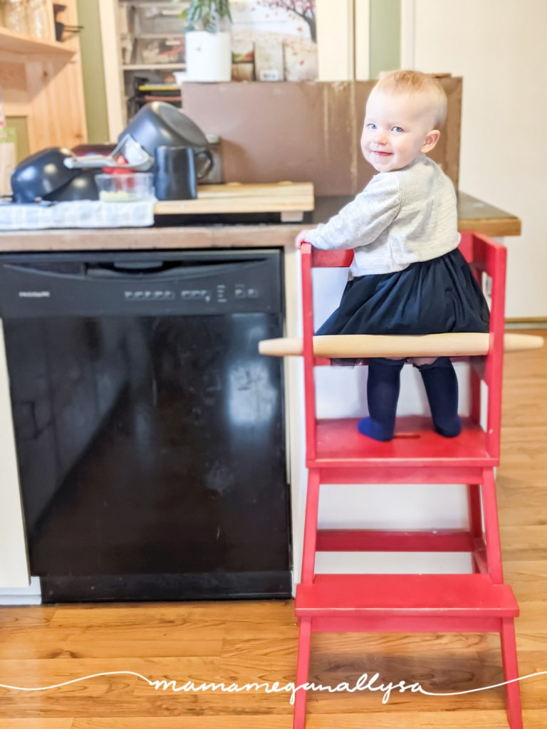a baby standing in a learning tower in the kitchen
