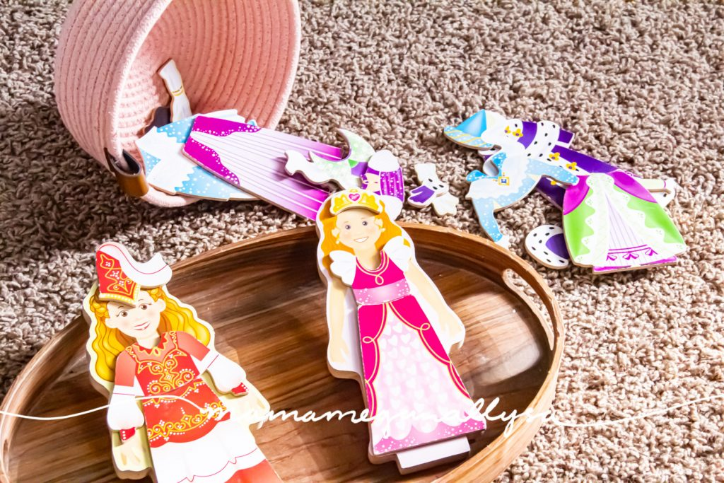 a close-up shot of two wooden magnetic dress-up princess dolls and their clothes in the background