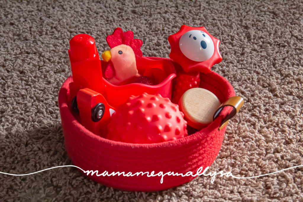 a close up shot of our red discovery basket filled with a random assortment of red baby toys