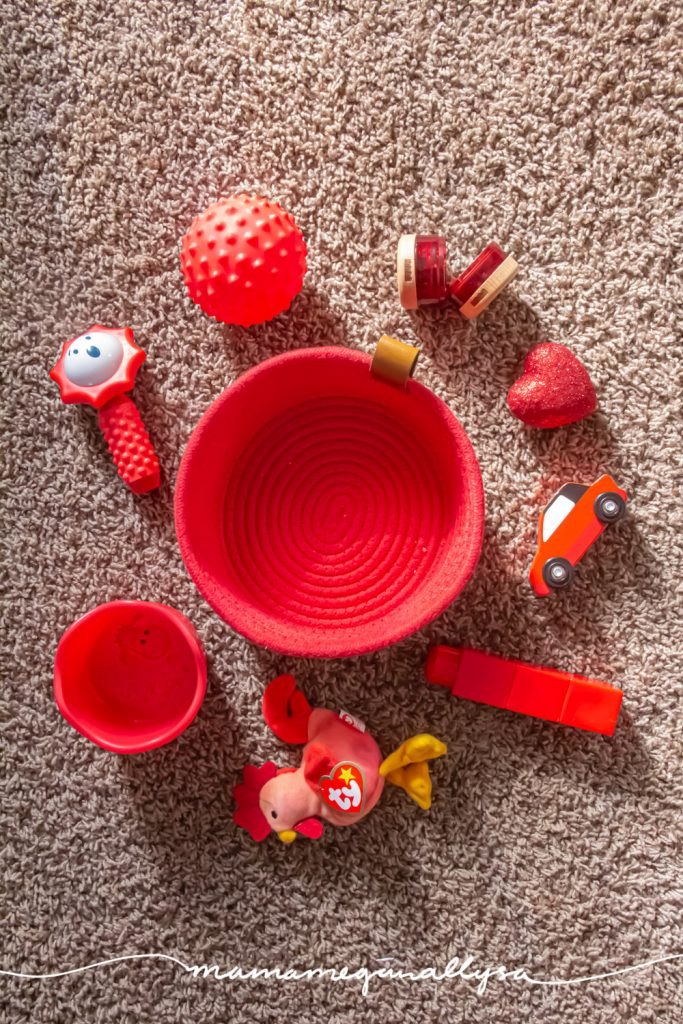 a top-down view of a red rope basket surrounded by a random collection of red baby toys