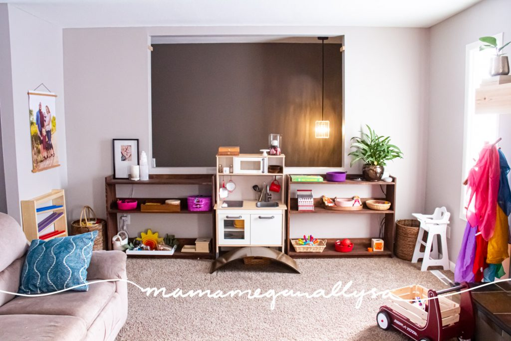 a look at our toy wall in our living room playroom with two play shelves and a play kitchen in between